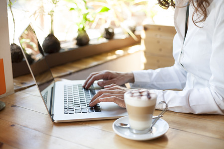 teclado: mujer con camisa blanca escribiendo en la computadora portátil de la PC teclado y cappuccino café listo pensando en luz de la tabla de madera marrón