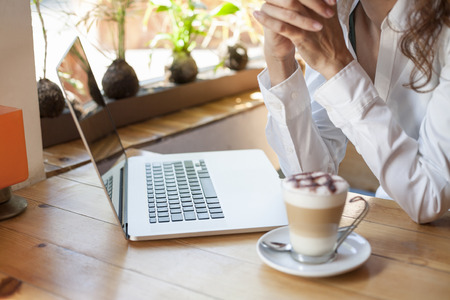 woman with white shirt in front of keyboard pc laptop and cappuccino coffee cup ready thinking on light brown wooden table Stock Photo