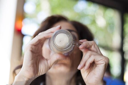 capuchino: portrait of woman drinking cappuccino coffee finishing cup in hands in cafe Stock Photo