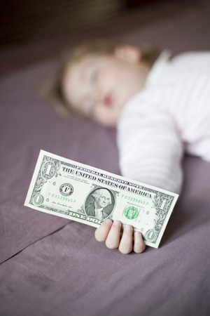 closeup one dollar banknote in hand of blonde caucasian baby nineteen month age with pink and white stripped jersey sleeping on brown sheets king bed