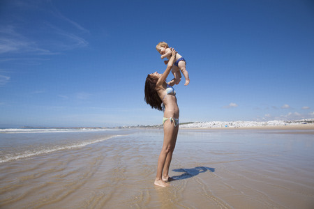 relationship mother and daughter: one year baby swimsuit fly in bikini woman mother arms at beach next to Conil Cadiz Spain