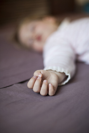 somnolent: closeup hand of blonde caucasian baby nineteen month age with pink and white stripped jersey sleeping on brown sheets king bed