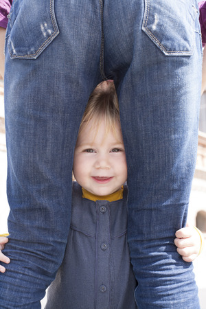 the lovely boy: blonde nineteen month age baby with blue and yellow dress between mother blue jeans back woman legs looking at camera Stock Photo