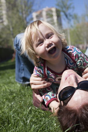 blond boy: two years aged blonde happy baby colored shirt hugging with brunette woman mother with black sunglasses lying on green grass lawn Stock Photo
