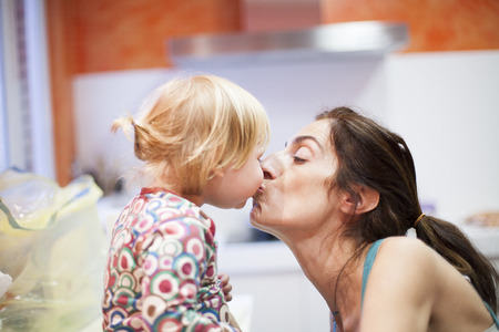 nineteen month aged blonde baby colored shirt with pigtails and brunette woman mother kissing in mouth in orange kitchen