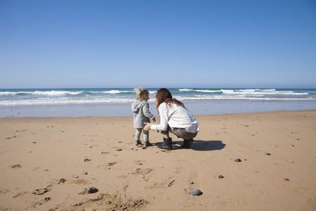 squatting: two years age blonde baby with grey coat and brunette mother woman squatting in sand of beach in front of water sea or ocean