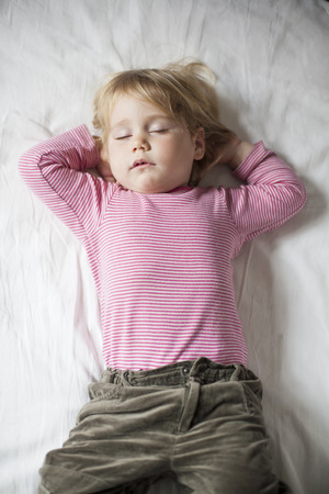 somnolent: blonde caucasian baby face two years old age with red striped shirt sleeping on white sheets with hands down her head