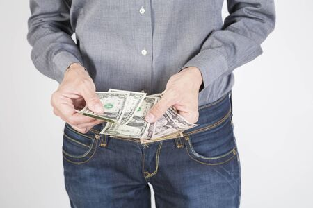 woman blue jeans trousers and grey shirt counting currency money cash one five ten and twenty dollar banknotes in her hands isolated over white background