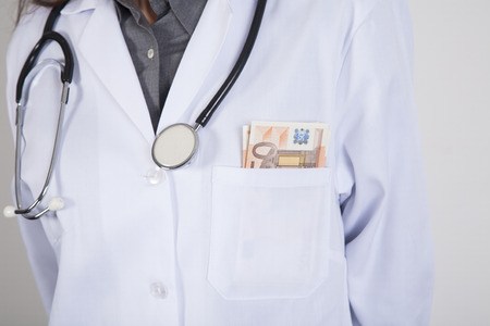 woman doctor with white gown and stethoscope with a wad of Euro banknotes in her pocket