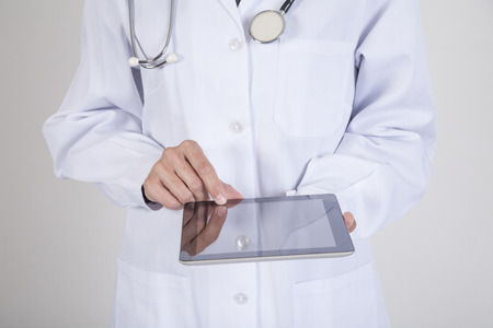 medical device: woman doctor hands with white gown and stethoscope using black blank screen mobile tablet over white background