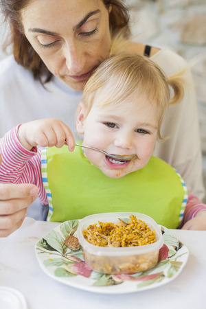 baby rice: portrait of two years age blonde baby with green bib eating rice paella from tupperware sitting on legs of mother woman in white table