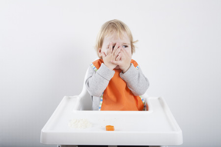 baby rice: blonde caucasian baby seventeen month age orange bib grey sweater eating meal in white high-chair with hands on eyes does not like carrot