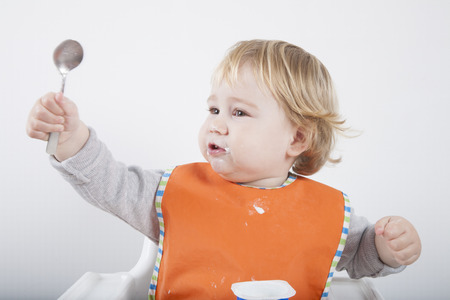 high chair: blonde caucasian baby seventeen month age orange bib grey sweater on white high chair with spoon hand up