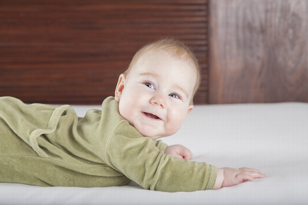 six months: six months age blonde baby green velvet onesie lying on white sheet bed with brown wood background smiling happy face Stock Photo
