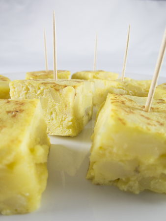 portions: little portions with toothpick of yellow spanish potato omelette on white dish