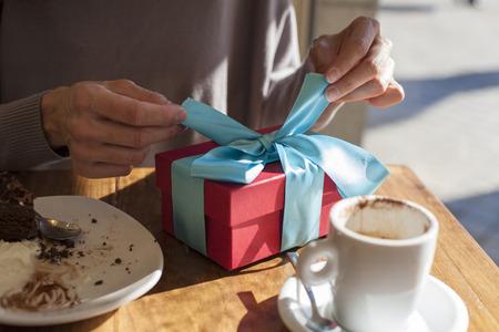 mujeres morenas: Mujer abierta caja de regalo de color rojo y azul en luz de la tabla de madera marr�n con blanco peque�a taza de caf� capuchino y pastel de chocolate plato