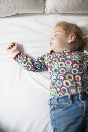 somnolent: blonde caucasian baby face nineteen month age with colored shirt sleeping on white sheets king bed