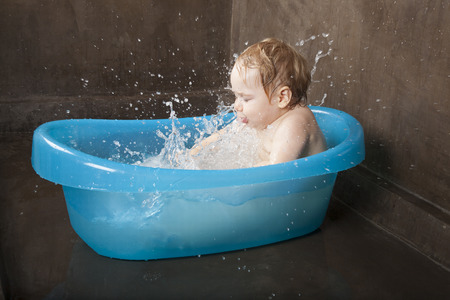bath: blonde baby washing in blue little bath indoor with brown background Stock Photo