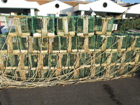 crab pots: stack of wooden fishing creels in Ribadesella public port Asturias Spain Europe Stock Photo