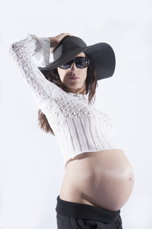 ombligo: ocho meses morena mujer embarazada vientre desnudo boca abajo suéter de lana botón superior gafas de sol negras gran sombrero posando pamela como modelo de manera aislada en blanco Foto de archivo