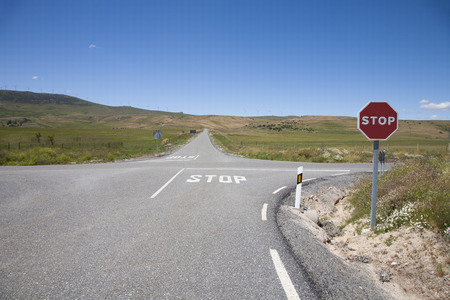 crossroads: crossroad with stop symbol painted on asphalt and red hexagonal signal metal pole in rural road next to Madrid Spain Europe