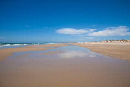 wet season: landscape from wet shore of Vejer Palmar Beach seaside with golden sand, blue green turquoise ocean water, waves and horizon blue clean sky in Cadiz Andalusia Spain