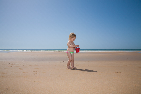 enfant qui joue: two years old back blonde baby with pink and green swimsuit walking with red plastic bucket in hand at golden sand beach seaside in Cadiz Andalusia Spain