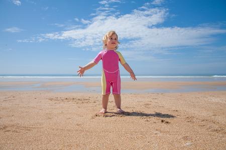 traje de bano: dos a�os de edad del beb� rubio con rosa y traje de ba�o amarillo coloca en la playa playa de arena dorada con pedir agua del oc�ano o hablando, hablando, contando con alguien fuera de la pantalla