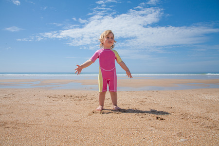 blond girl: two years old blonde baby with pink and yellow swimsuit standing at golden sand beach seaside with ocean water asking or talking to, speaking, telling to someone offscreen