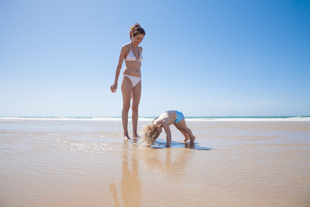 blonde bikini: summer family of two years old blonde baby with blue swimsuit playing on ground water with brunette woman mother in white bikini at sea shore beach sand in Cadiz Andalusia Spain Stock Photo