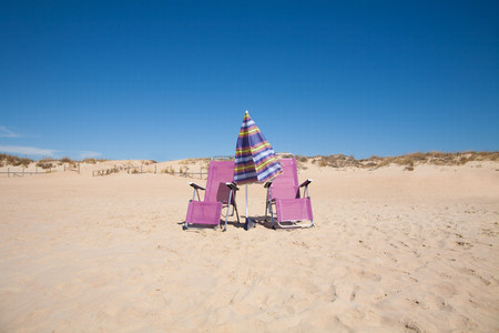 purple metal: two lonely purple metal front seat beach chairs and umbrella parasol closed on sand at Vejer Palmar Beach, with horizon blue clean sky in Cadiz Andalusia Spain