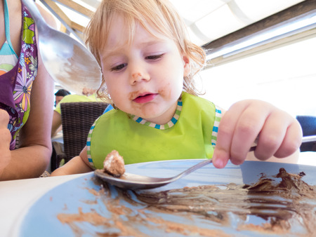 smeared baby: blonde baby two years old with green bib and silver metal spoon in her hand scraping and finishing chocolate cake in blue dish and smeared with chocolate sitting in restaurant next to woman mother