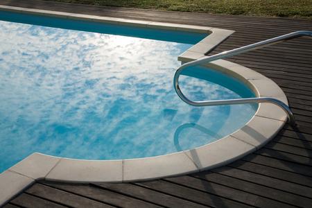 bajando escaleras: hermoso detalle de la piscina con el cielo nublado se refleja en el agua azul, acera de baldosas, escaleras abajo del agua, mango de metal y el piso de madera alrededor Foto de archivo