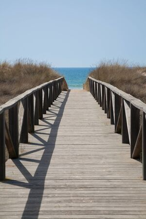 boardwalk trail: wooden walkway with hand rail with green blue turquoise water ocean or sea over nature in Vejer Palmar Beach seaside in Cadiz AndalusiaSpain