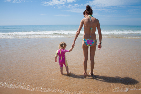 yellow bikini: summer back family of two years old blonde baby with pink and yellow swimsuit holding hand with brunette woman mother in bikini standing at sea shore beach sand in Cadiz Andalusia Spain