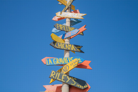 multidirectional: grey metal pole guidepost with multiple directional and distance to places of the world on wooden arrows yellow, red and grey sticks with blue sky Stock Photo