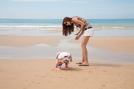 babysitter: summer family of two years old blonde baby with pink hat white shirt and colorful trousers with woman mother or babysitter white jeans shorts looking for, picking and collecting sea shells at golden sand beach seaside Stock Photo
