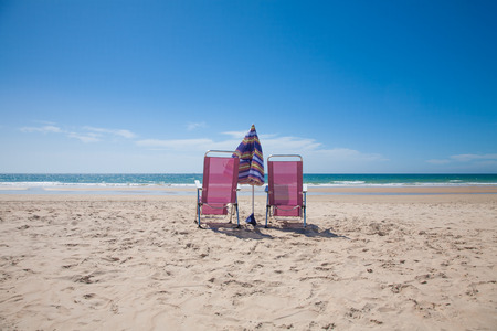 purple metal: two lonely purple metal back seat beach chairs and umbrella parasol closed on sand at Vejer Palmar Beach, with horizon blue clean sky in Cadiz Andalusia Spain