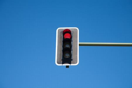 semaforo rojo: la luz del semáforo semáforo rojo en luces de color naranja y verde apagado en polo verde en el cielo azul horizontal Foto de archivo