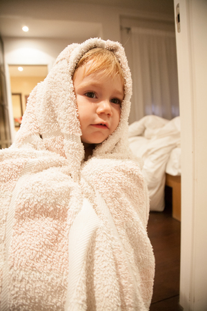 two years: blonde caucasian baby two years old age chubby face wrapped in white bath towel looking indoor bedroom home