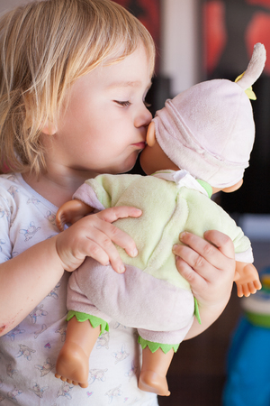 girl friend: lovely and tender scene of blonde caucasian cute baby two years old kissing on the cheek or talking to ear a doll in hands indoor