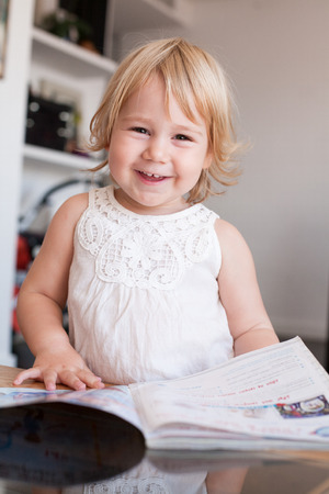 two years: blonde caucasian baby two years old cute face looking at camera with happy smiling expression wearing a white dress or summer shirt thumbing and reading a magazine indoor home Stock Photo