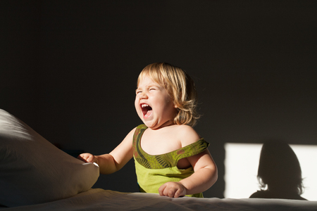 petite fille avec robe: portrait de b�b� caucasien deux ans debout avec une robe verte bouche ouverte et les cris du soleil sur le visage dans une pi�ce sombre � l'int�rieur Banque d'images