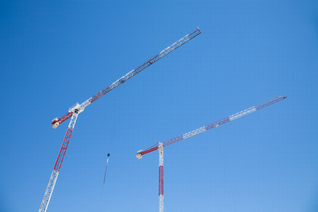 hoist: underneath view of red and white steel crane hoist in construction work and blue sky in urban street in Madrid city Spain Europe Stock Photo