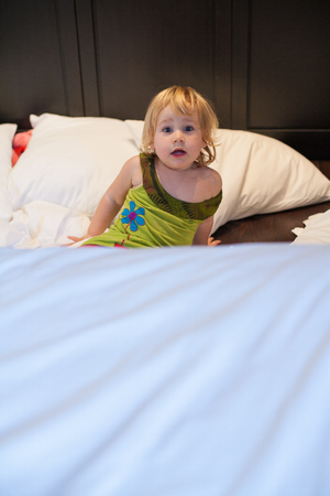 red shorts: blonde caucasian baby two years old with green dress red shorts lying on bed white clothes and cushions crying on dark wood floor