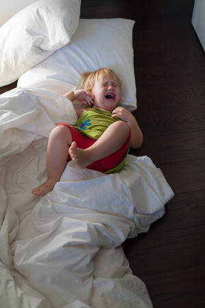 gente triste: blonde caucasian baby two years old with green dress red shorts lying on bed white clothes and cushions crying and screaming on dark wood floor