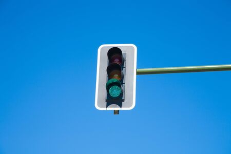 light speed: traffic light semaphore green light on orange and red lights off  in green pole on blue sky horizontal
