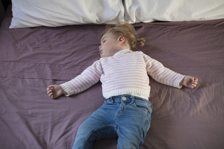 somnolent: blonde caucasian baby nineteen month age with blue jeans trousers pink and white stripped jersey sleeping on brown sheets king bed