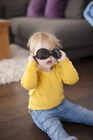 the lovely boy: two years aged blonde happy baby yellow shirt and blue jeans playing with black sunglasses of woman adult sitting on wooden indoor floor and looking at camera