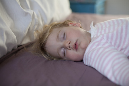 somnolent: blonde caucasian baby nineteen month age with pink and white stripped jersey sleeping on brown sheets queen bed